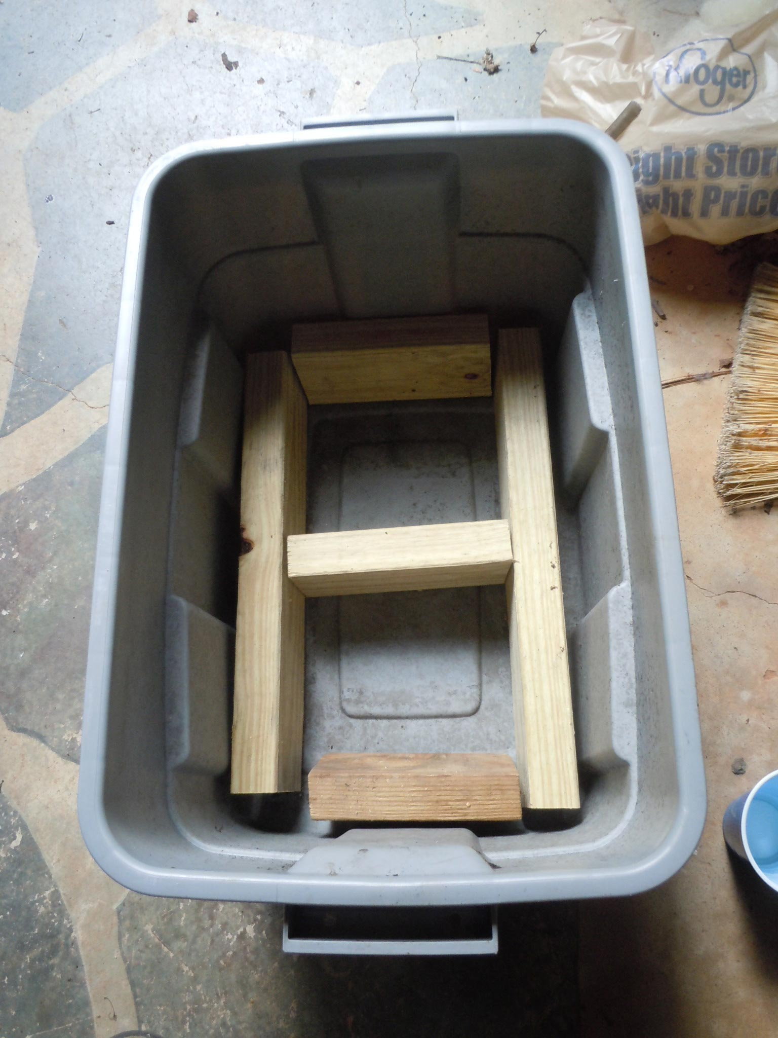 """cut pressure treated 2""""x4"""" lumber to fit inside and support the plastic lid"""